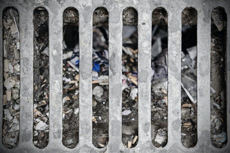 Dirty sewer on a street. Urban pollution. Grunge drain